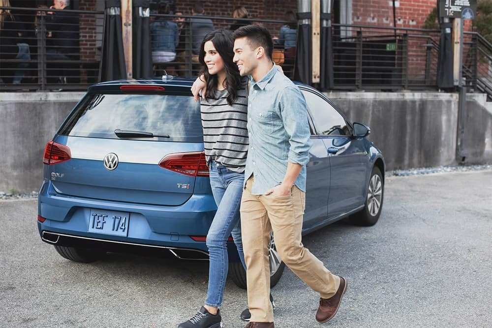 Couple walking past 2018 Volkswagen Golf