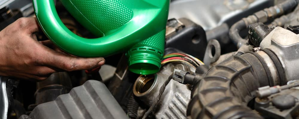 Auto Mechanic Changing Oil Close Up
