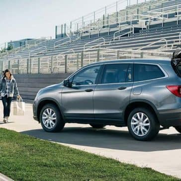 Family walking to a 2019 Honda Pilot parked on football field sidelines