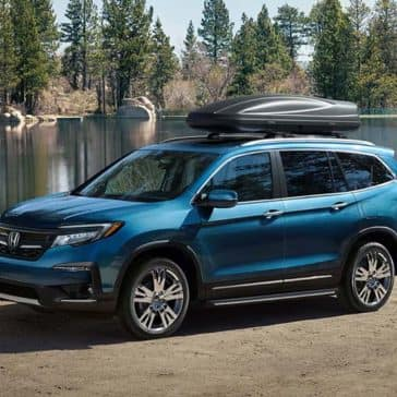 2019 Honda Pilot parked at a lake with family camping nearby