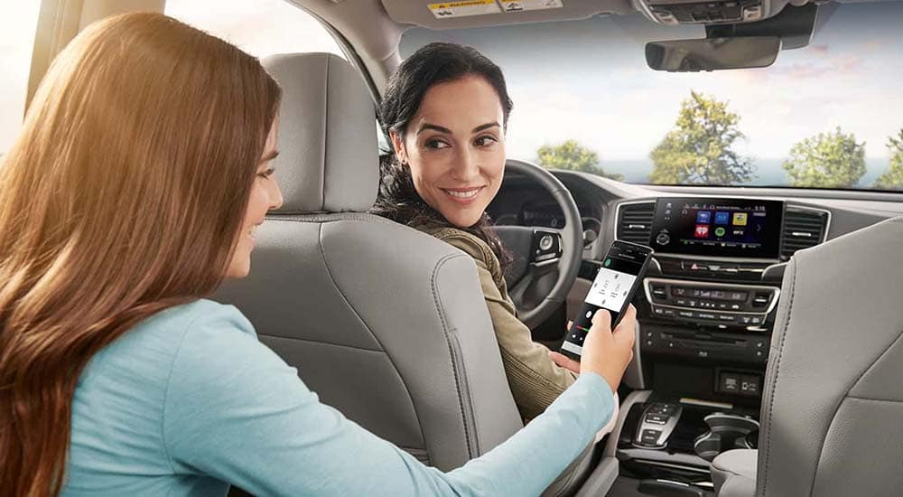 Mom and daughter connecting cell phone to 2019 Honda Pilot