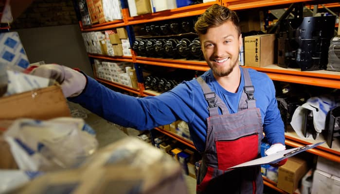 Smiling technician reaching for automotive parts in warehouse