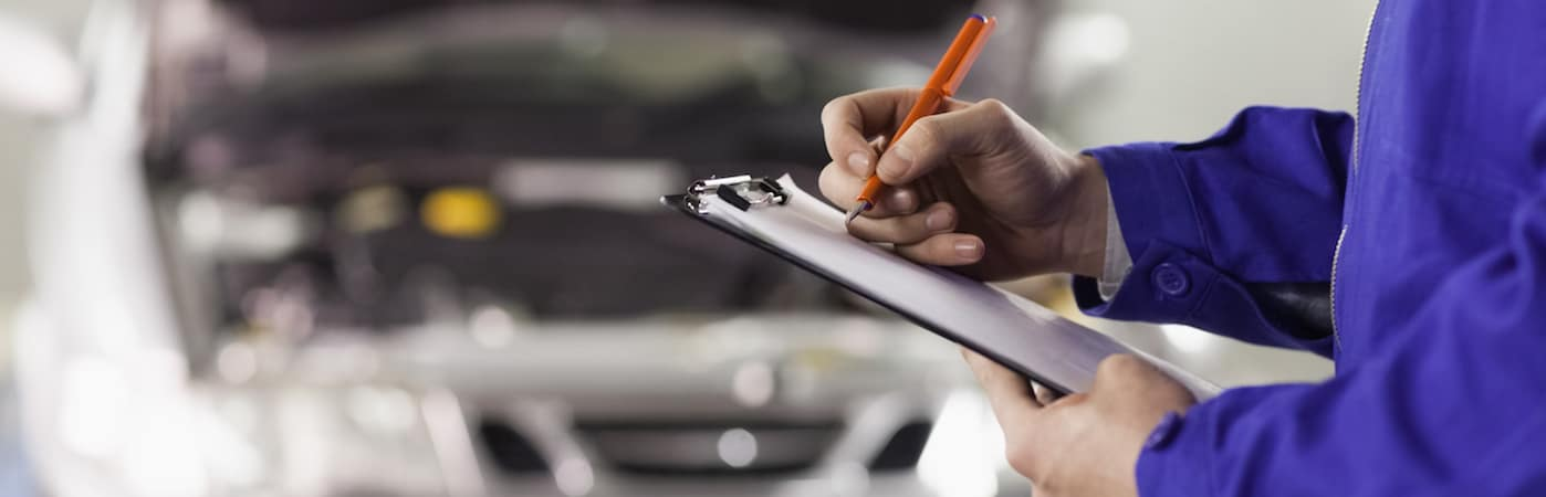 Service technician writing on clipboard standing near car with open hood