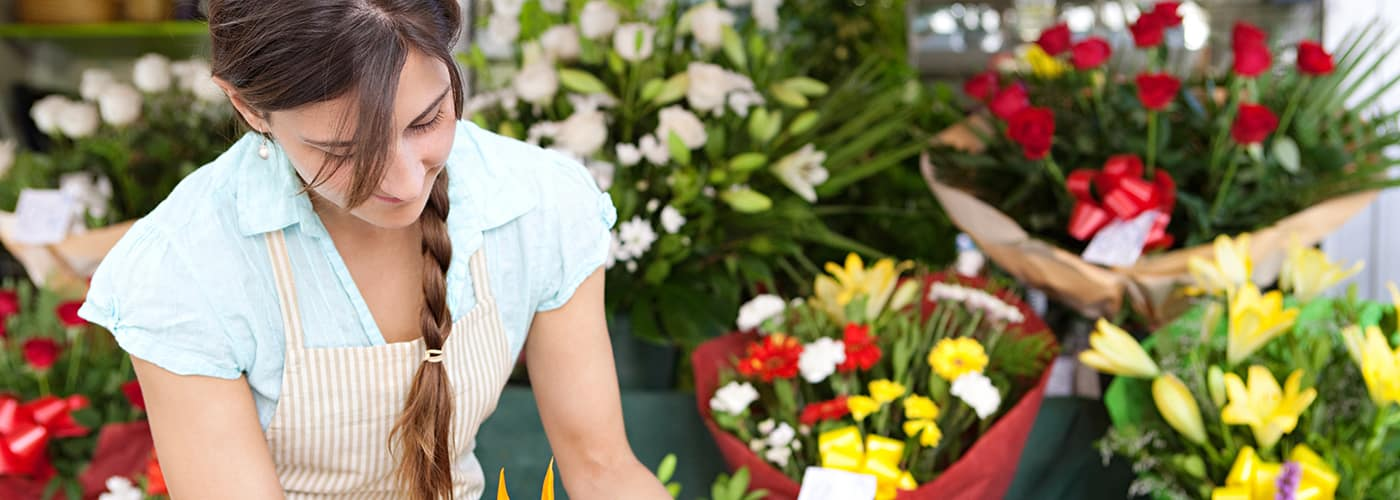 woman arranging flowers at shop