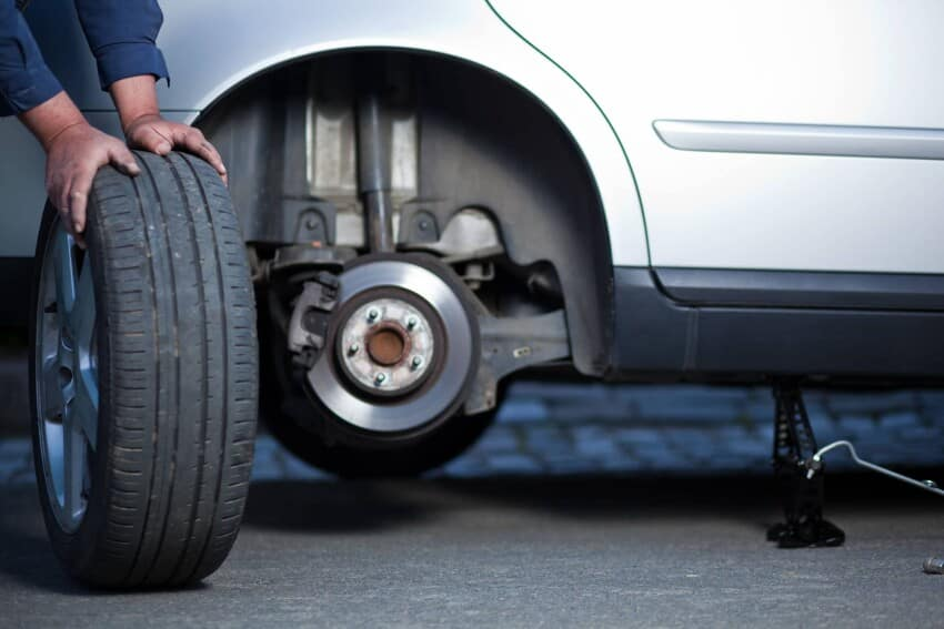 Mechanic Rolling Tire Away
