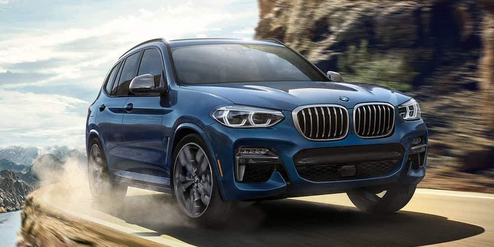 Blue 2019 BMW X3 Driving Around Canyon Corner