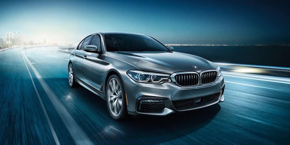 Silver 2020 BMW 5 Series Driving Down Highway