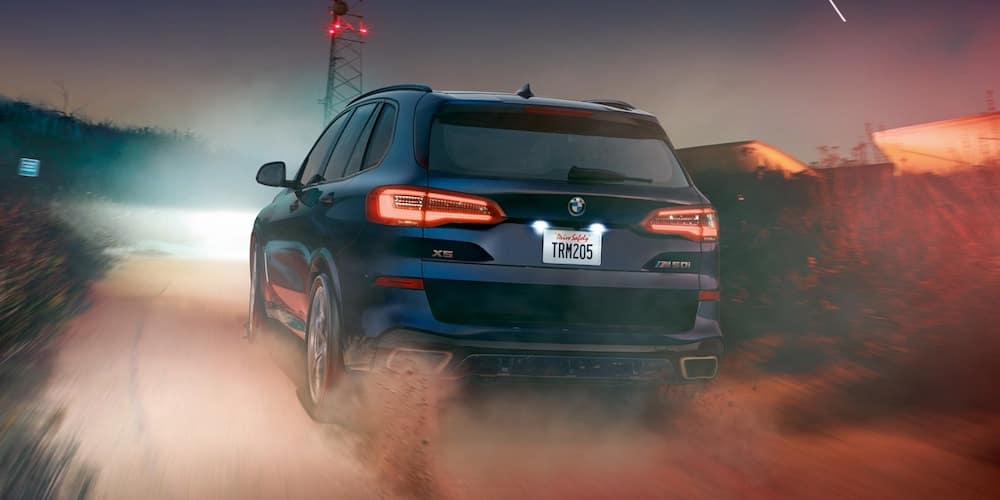 Blue 2020 BMW X5 M50i Driving on Dirt Road