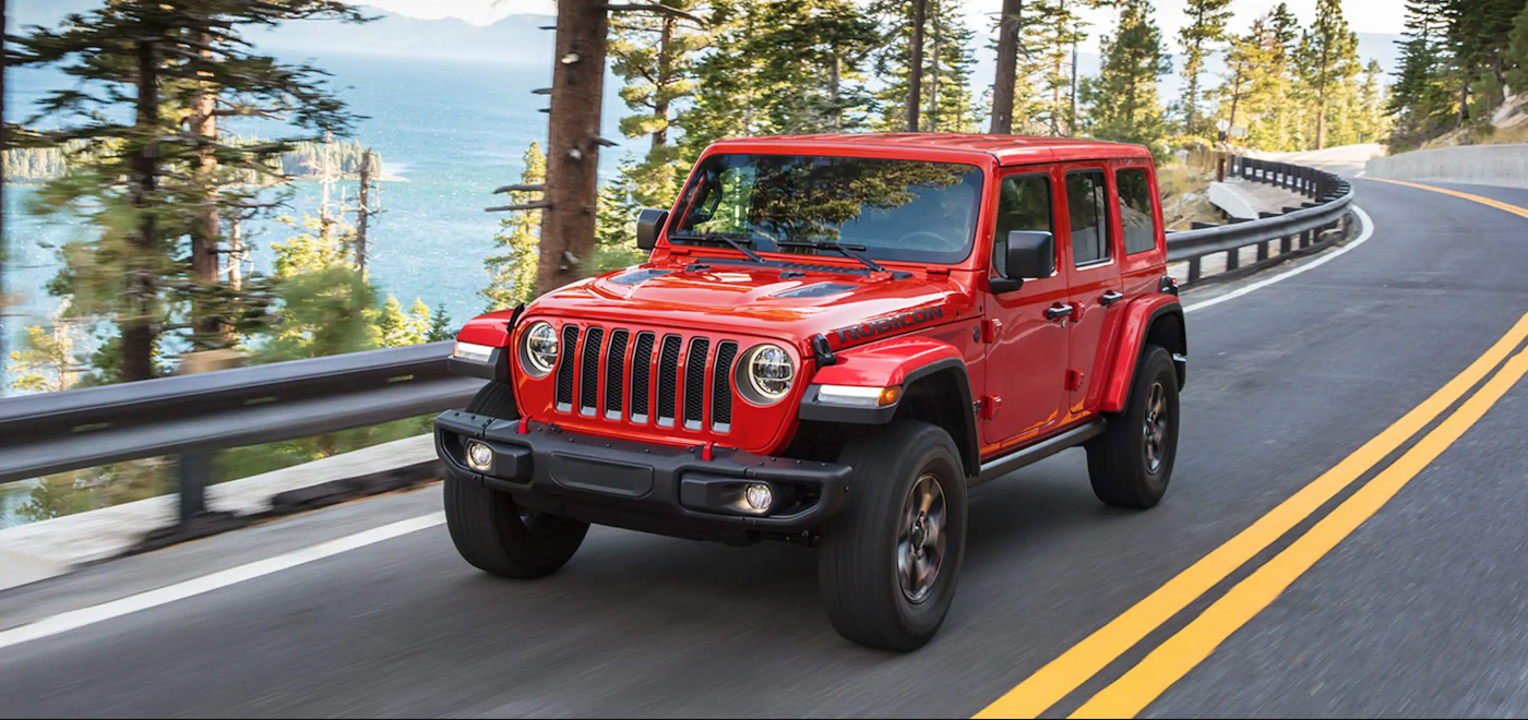 The 2021 Jeep Wrangler driving on a winding road.