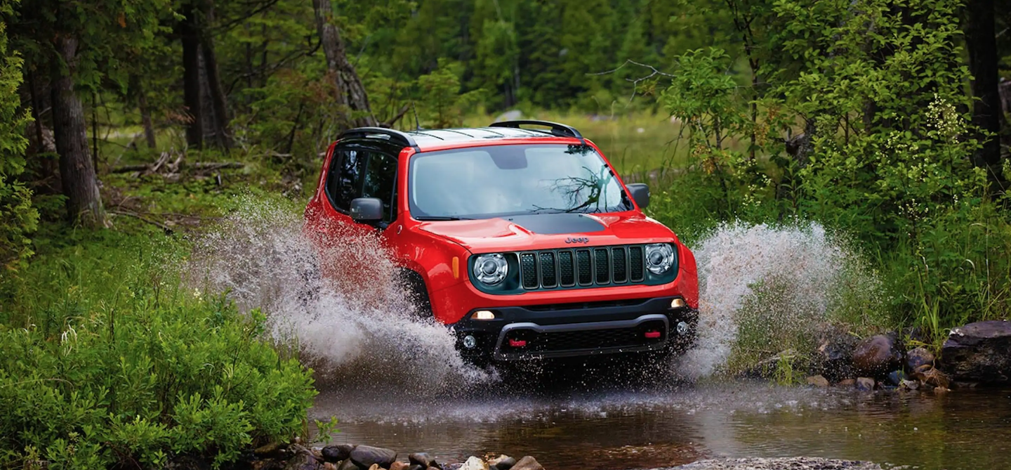 2021 Jeep Renegade driving through water in the woods.
