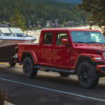 A red 2021 Jeep Gladiator towing a boat.
