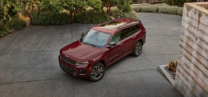 A red 2021 Jeep Grand Cherokee L parked outside of someones home.