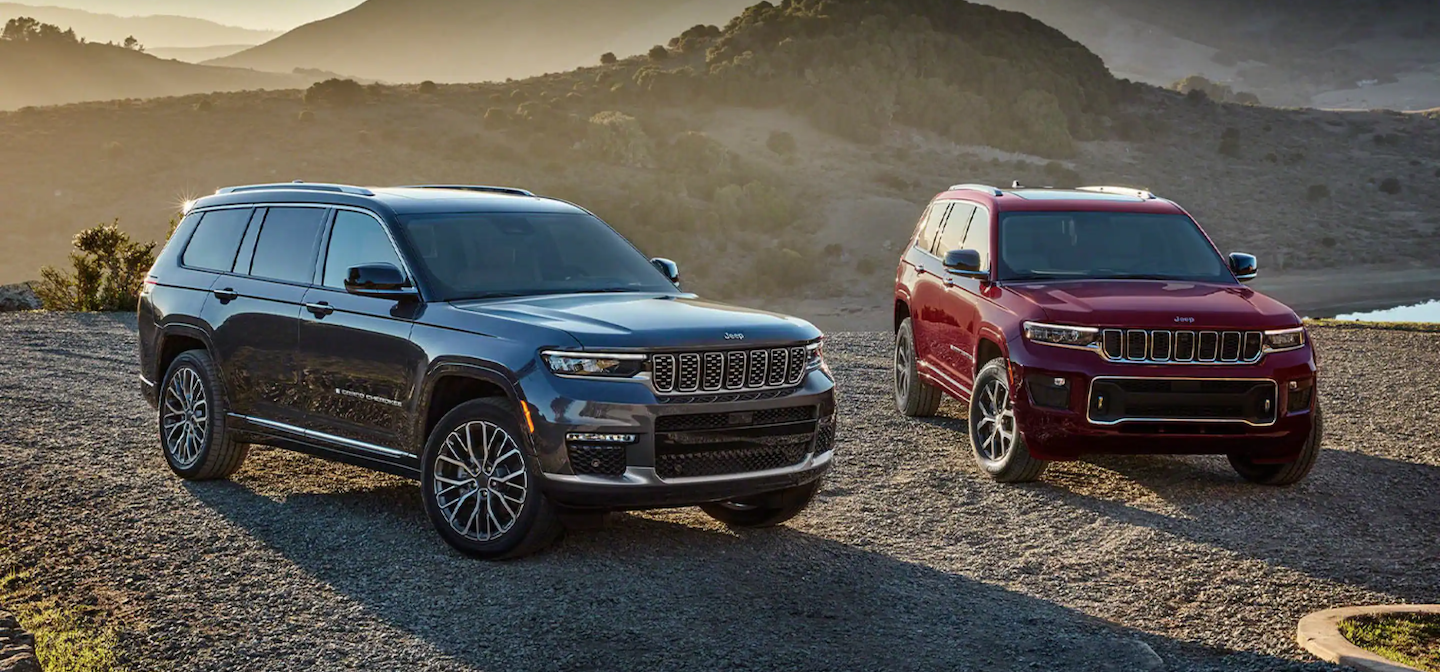 Two 2021 Jeep Grand Cherokee L vehicles parked in the desert.