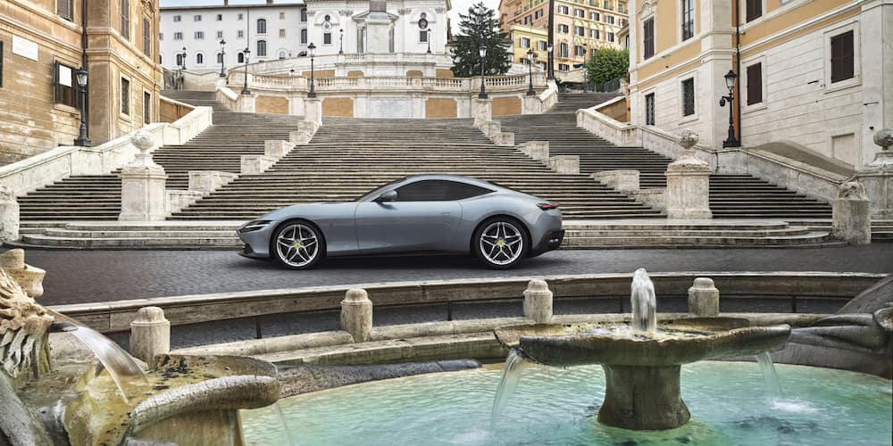 Ferrari Roma parked in front of a fountain