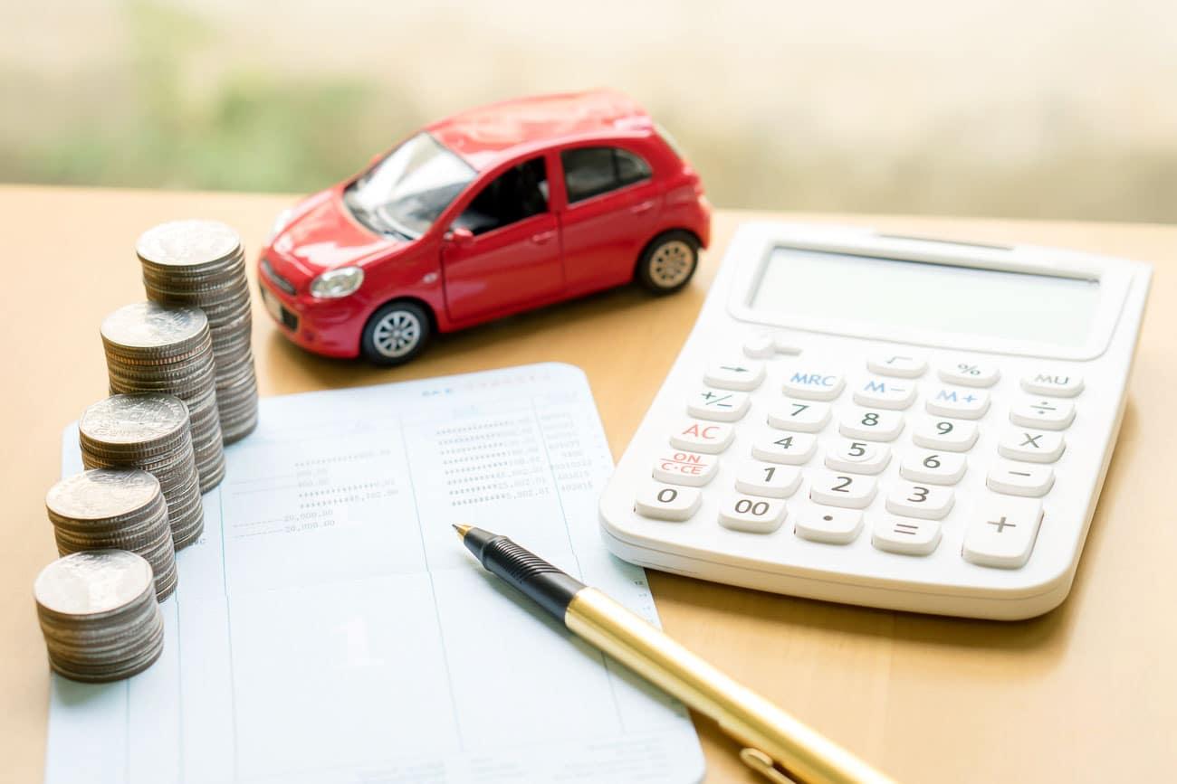 coins car and calculator on a desk