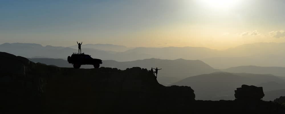 People and Jeep Wrangler on Mountain top