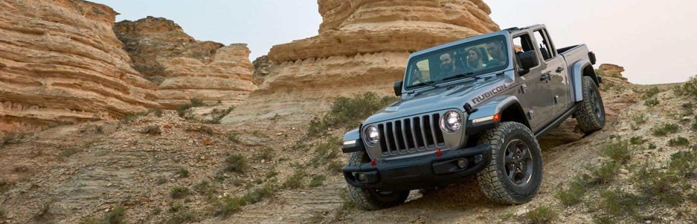 A 2020 Jeep Gladiator driving down a dirt hill