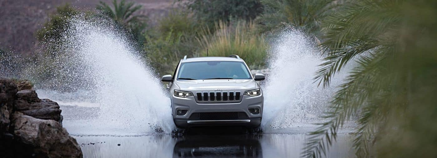 A 2020 Jeep Compass driving through a shallow river