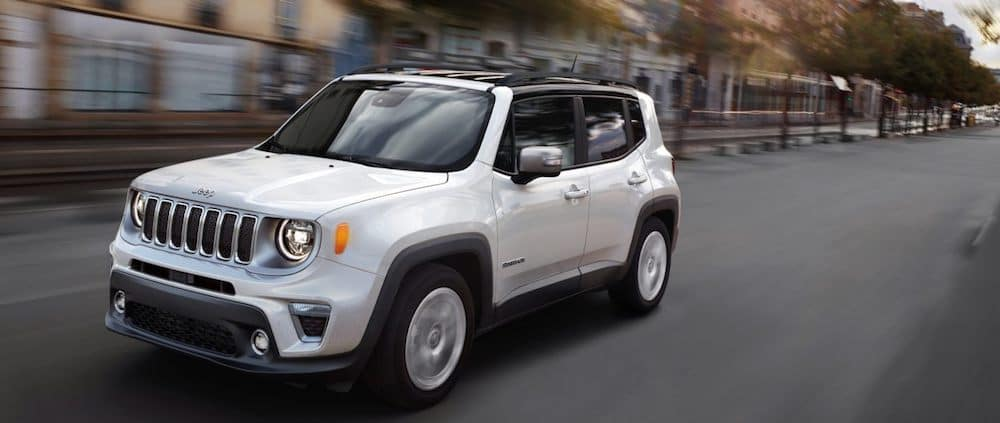 A white 2020 Jeep Renegade driving on a city street