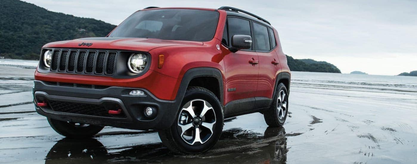 A red 2020 Jeep Renegade is driving on a wet beach.