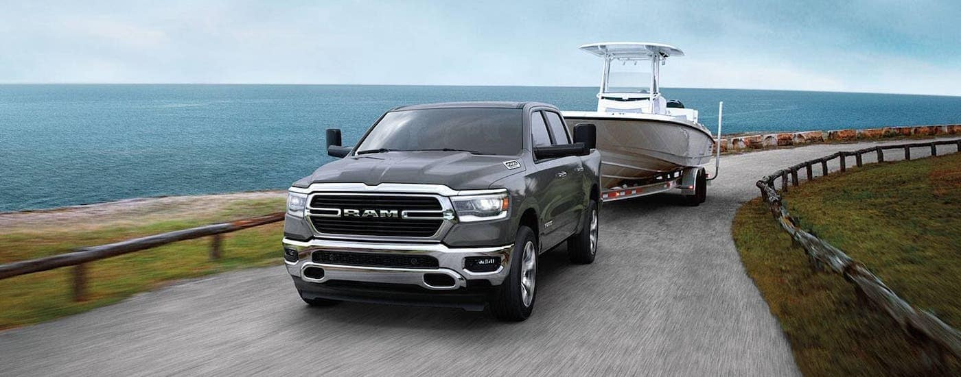 A gray 2020 Ram 1500 is towing a boat with an ocean behind it.