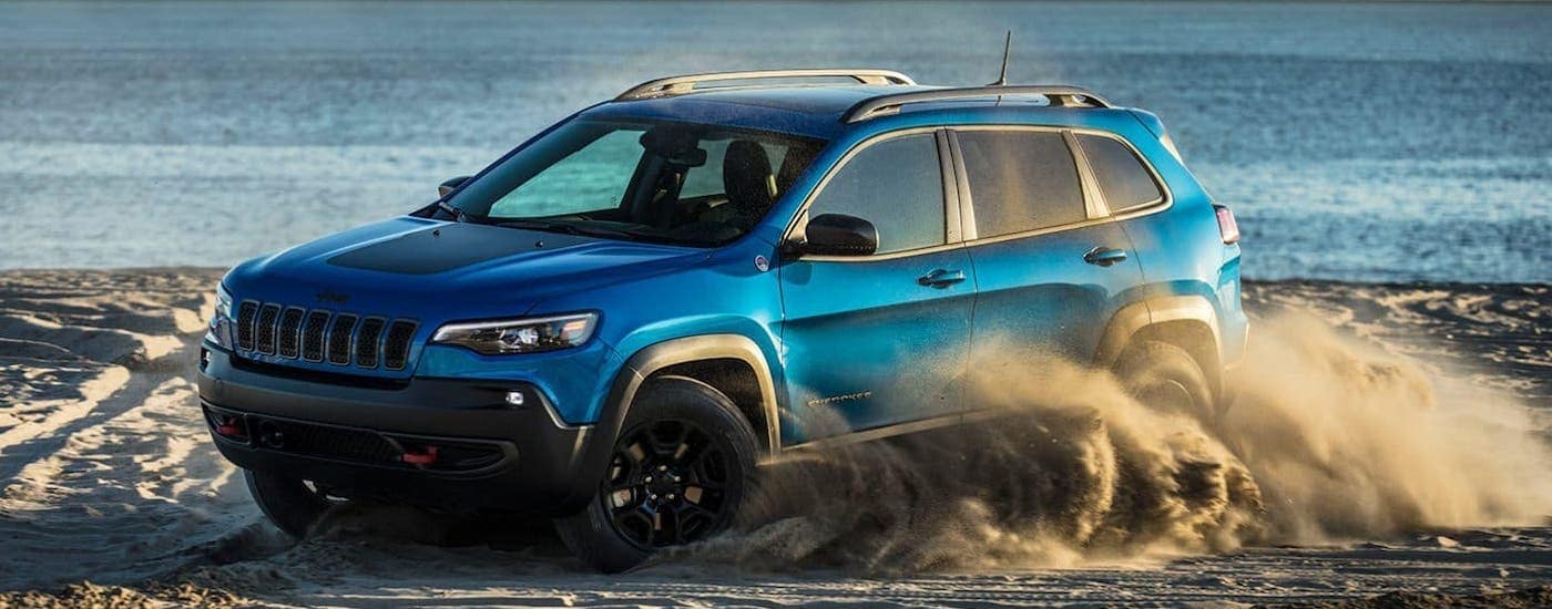 A blue 2020 Jeep Cherokee Trailhawk is kicking up sand on a beach.