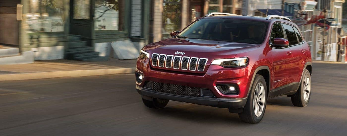A red 2020 Jeep Cherokee is driving on a street near Lexington, KY.