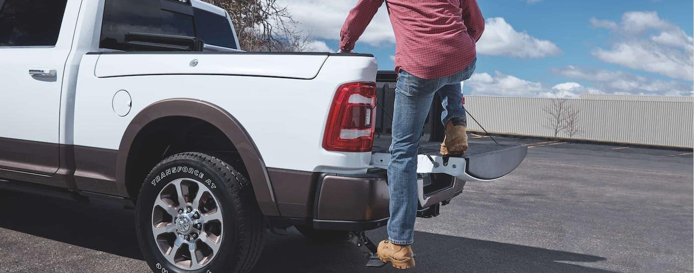A man is using the rear step to climb into a white 2020 Ram 2500.