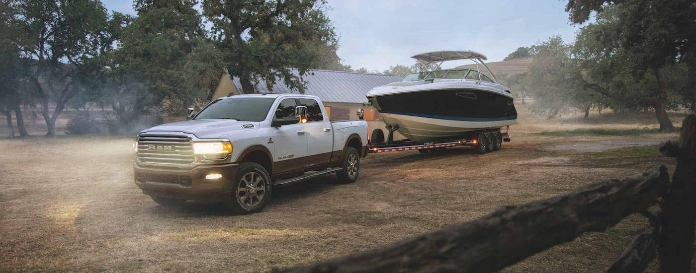 A white 2020 Ram 2500 is towing a boat at a farm near Lexington, KY.