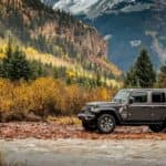 A grey 2018 Jeep Wrangler Unlimited is parked off-road in front of a river and mountains.