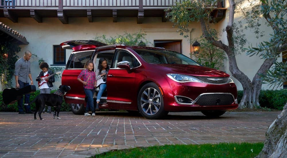 A family is about to get into a red 2017 Chrysler Pacifica.