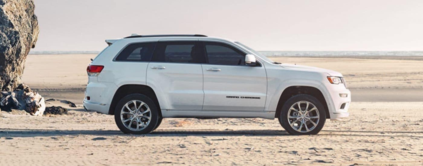 A white 2019 Jeep Grand Cherokee is shown from the side while parked on a beach.