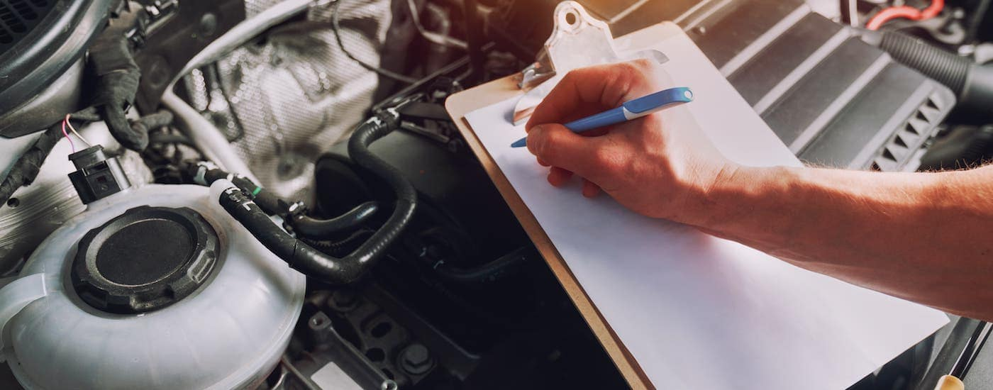 A closeup shows a clipboard while a mechanic inspects a car's engine.