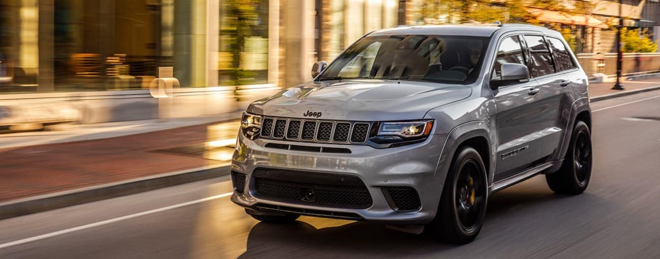 A grey 2020 Jeep Grand Cherokee is driving on a city street near Lexington, KY.