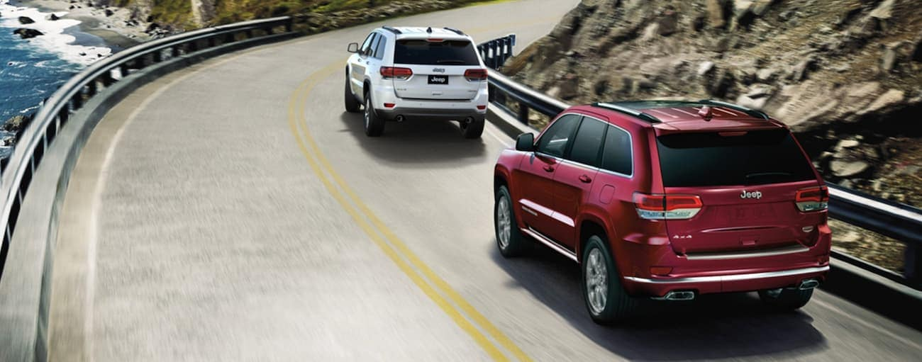 A red 2020 Jeep Grand Cherokee is following a white one around a corner past the ocean.