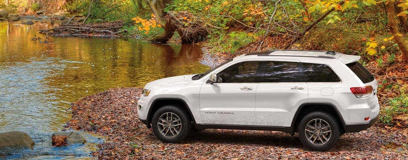 A white 2020 Jeep Grand Cherokee is parked on a rocky river bank.