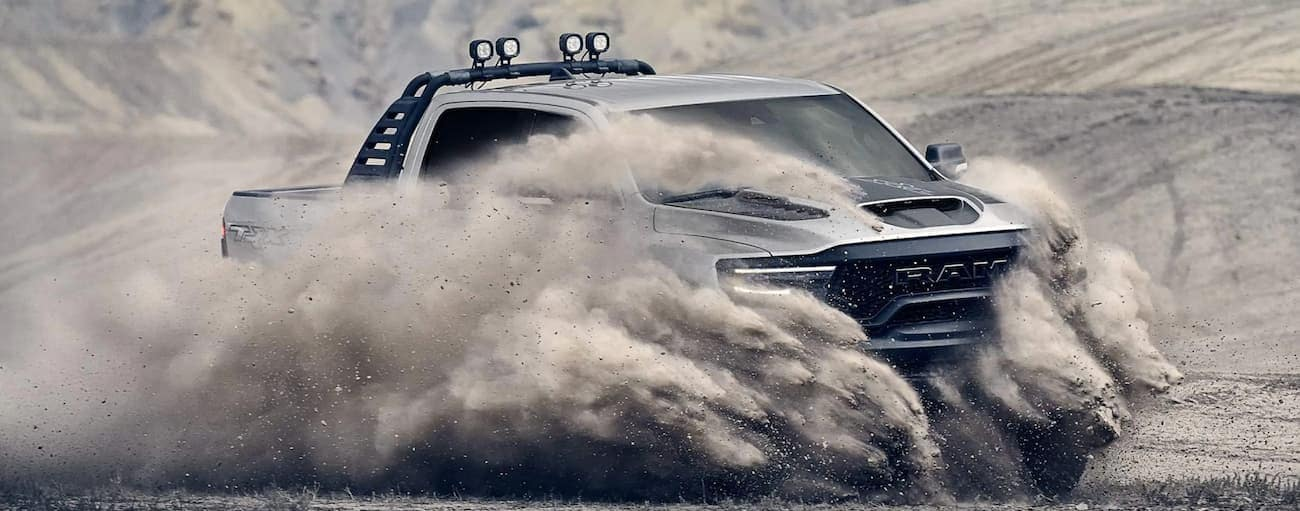 A silver 2021 Ram 1500 TRX is covered in a cloud of dust while off-roading on a sand dune.