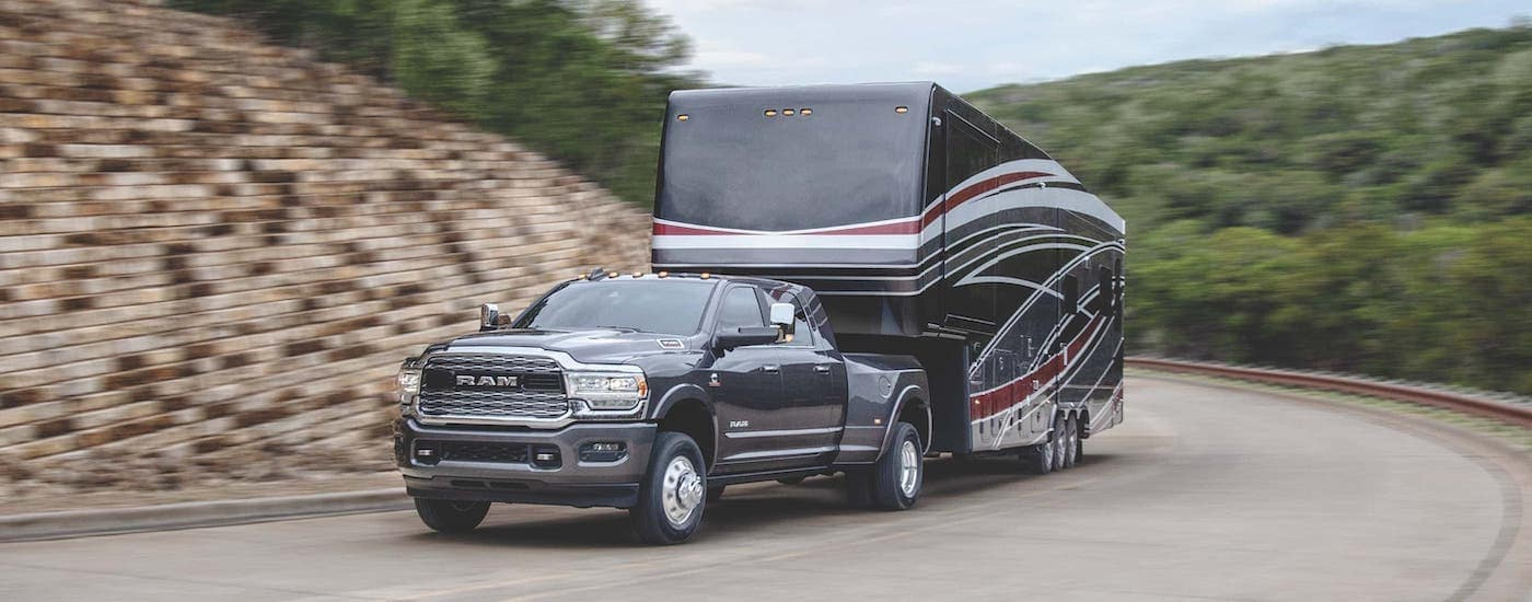A gray 2020 Ram 3500 is towing a trailer around a corner.