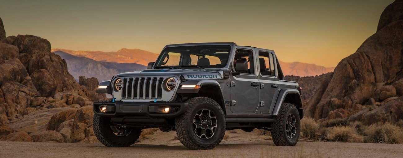 A silver 2021 Jeep Wrangler 4xe is parked in the desert at sunset.
