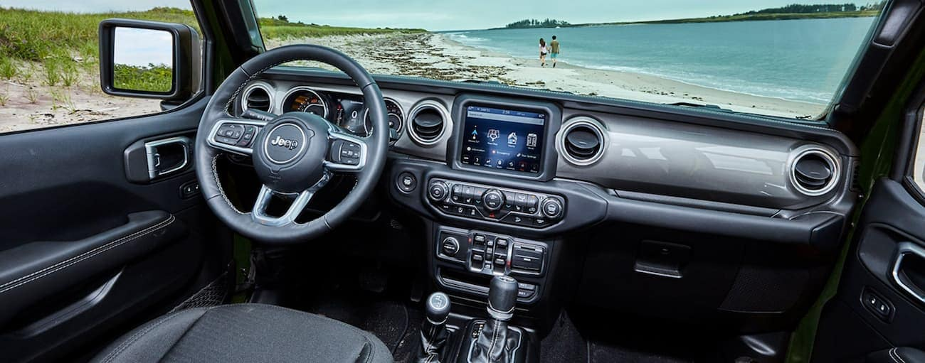 The black interior is shown in a 2021 Jeep Wrangler with a beach in the windshield.