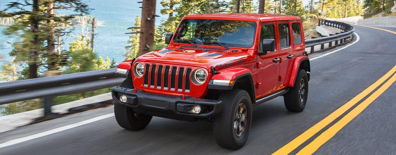 A red 2021 Jeep Wrangler Rubicon is driving past pine trees on a mountain road.