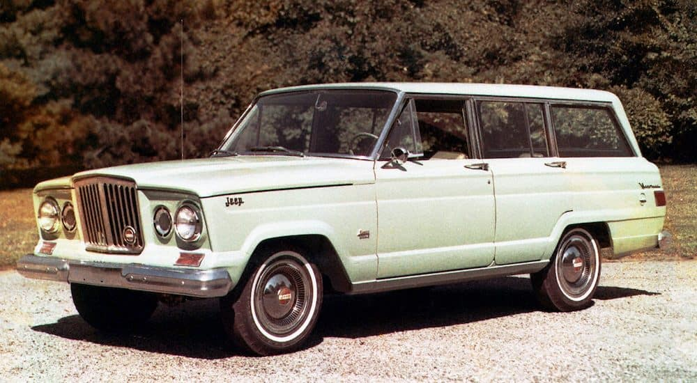 A pistachio 1962 Jeep Wagoneer is parked on the asphalt after leaving the Jeep dealer near you.