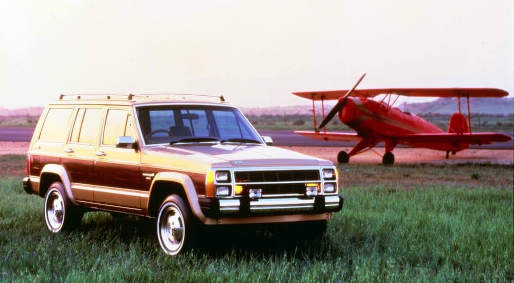 A brown 1984 Jeep Wagoneer is parked in front of a red biplane.