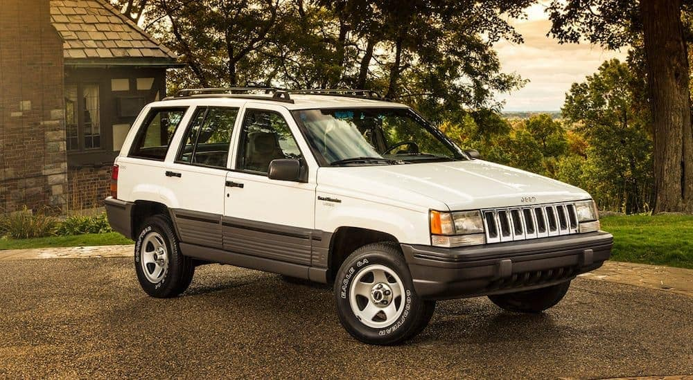 A white 1995 used Jeep Grand Cherokee is parked angled right with a cabin and forest in the background.