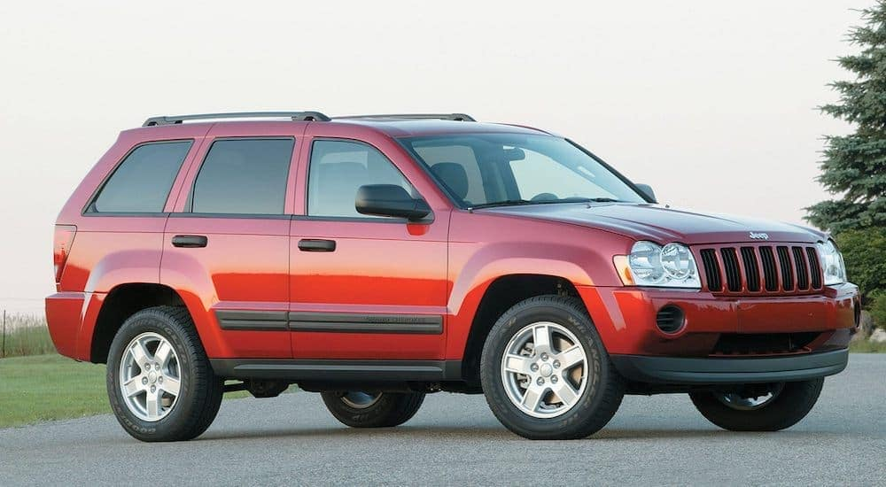 A red 2006 used Jeep Grand Cherokee is parked with blue sky in the background shown from a low angle.