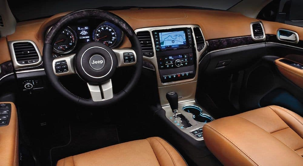 The tan and black interior is shown on a 2016 used Jeep Grand Cherokee.