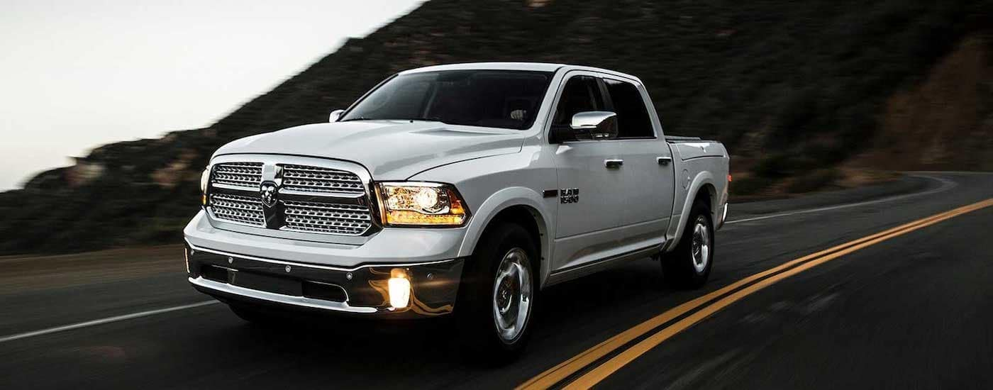 A silver 2015 Ram 1500 is shown driving down an empty road.