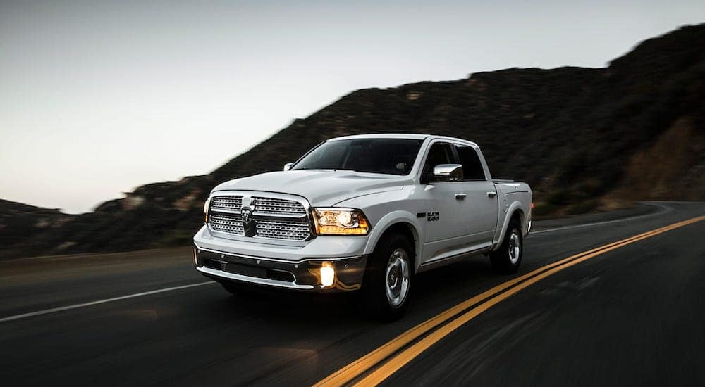 A silver 2015 used Ram 1500 is driving down the road.