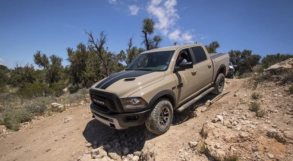 A tan and black 2017 used Ram 1500 is driving down a rocky hill.