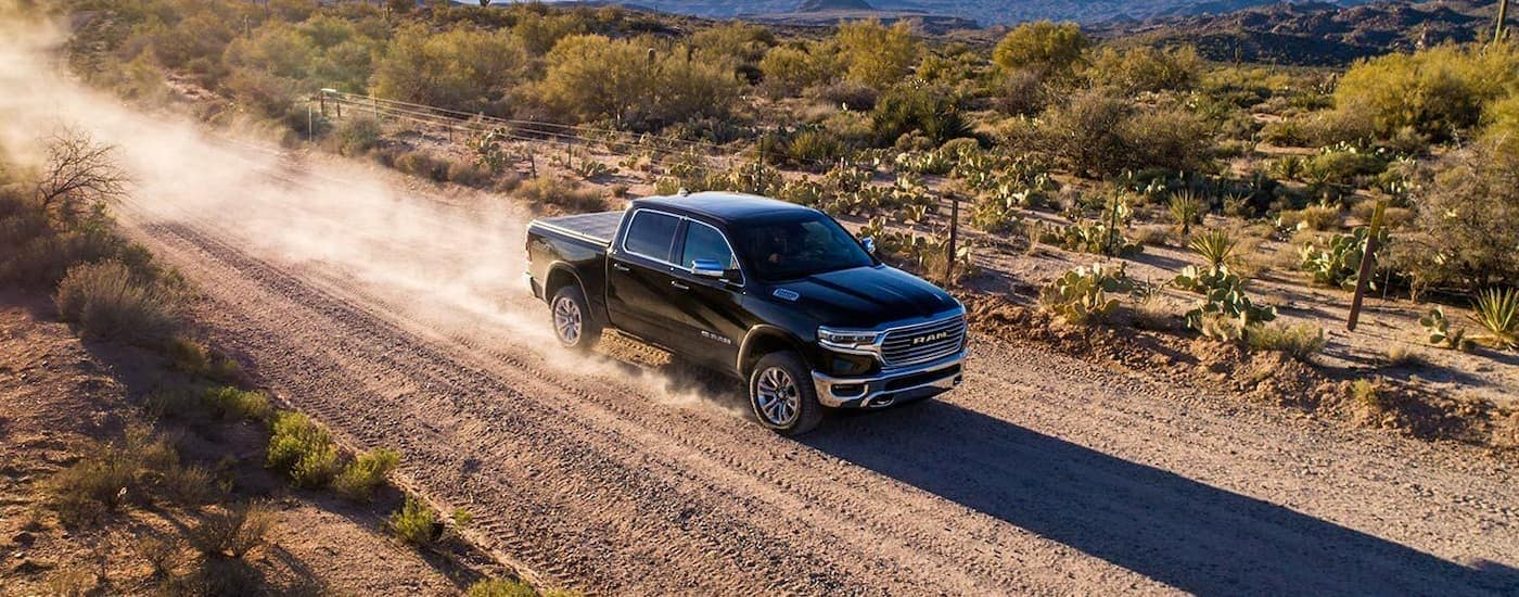A black 2019 used Ram 1500 is driving on a rural dirt road with a dust trail.